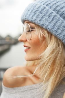 Perfil de impresionante mujer rubia con gafas, sombrero azul y suéter gris