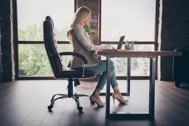 El perfil lateral de reflexionar pensativa dama de negocios en zapatos de tacón mirando a la pantalla del portátil