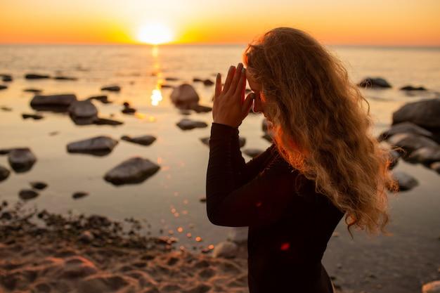 Perfil de la mujer joven que se relaja en la playa, meditando con las manos en el gesto de namaste en la puesta del sol o la salida del sol, cierre para arriba.