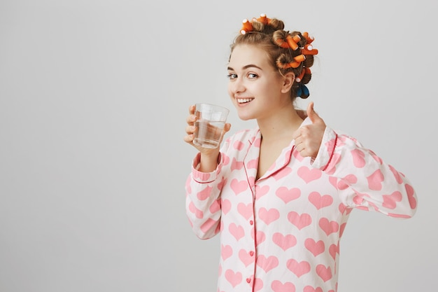 Perfil de mujer joven con rizadores de pelo bebiendo agua en pijama muestran thumbs-up