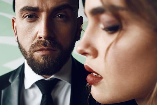 Perfil de una mujer con labios rojos de pie delante de un hombre