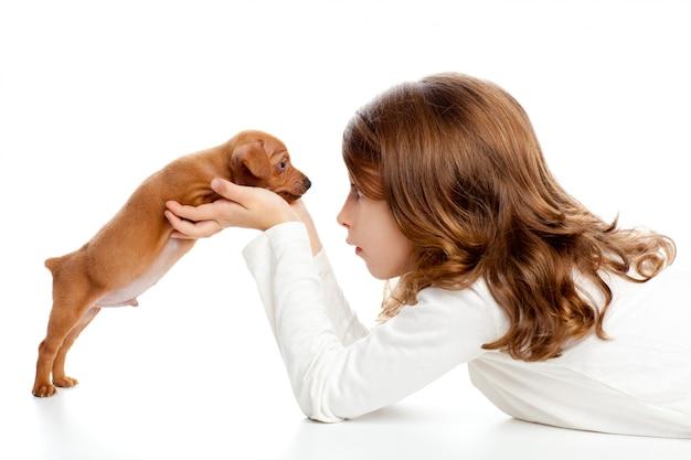 Perfil de niña morena con perro cachorro mini pinscher