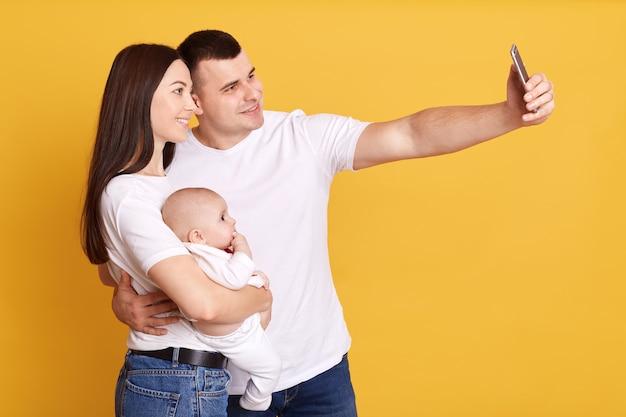 Perfil de pareja feliz tomando selfie con bebé en manos, mirando con expresiones faciales alegres en la parte delantera del dispositivo, pareja con hija pequeña aislada sobre pared amarilla.