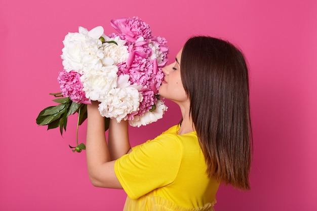 Perfil de tierna hermosa hembra linda con flores en ambas manos, cerrando los ojos, levantando peonías blancas y rosadas, sintiendo el olor de ellas, obteniendo placer del presente. gente y flores.