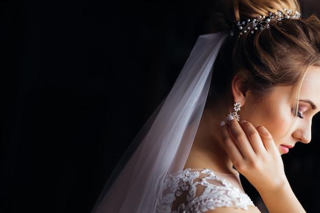 Perfile a la novia con velo de novia y el vestido blanco.