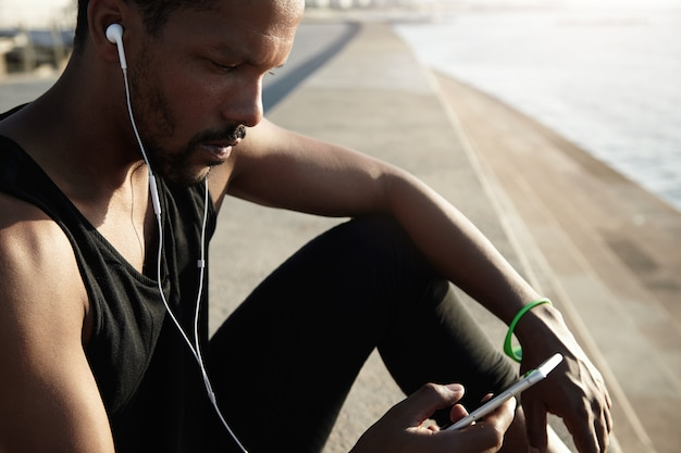 Perfile el retrato del oficinista negro en auriculares que descansa después de su entrenamiento al aire libre de la mañana, escuchando música, mirando la pantalla de su teléfono inteligente y eligiendo canciones favoritas de la lista de pistas