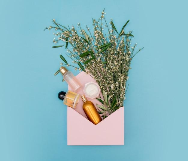 Perfume cosmético con botella dorada con hierbas y flores en sobre rosa sobre fondo azul. vista superior