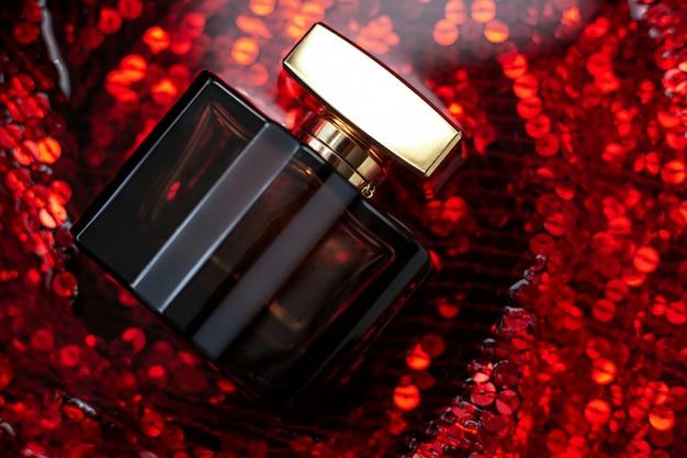 Perfume femenino sobre fondo rojo