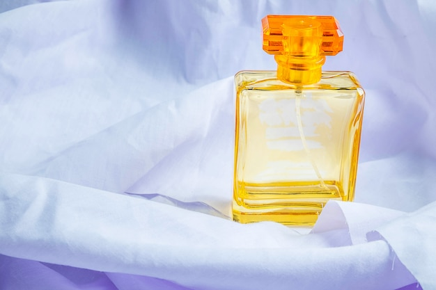 Perfume y frascos de perfume sobre un piso de tela blanca.
