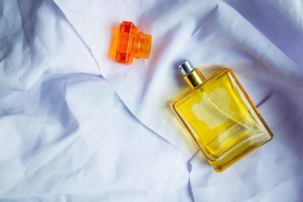 Perfume y frascos de perfume sobre un piso de tela blanca