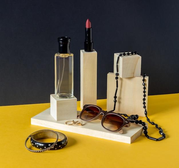 Perfume, pintalabios, vasos y abalorios. productos cosméticos. moda. minimalismo.