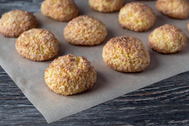 Pergamino con sabrosas galletas de coco en la mesa de woden