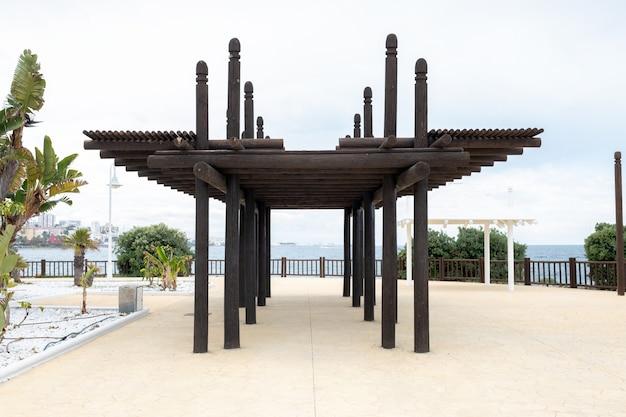 Pérgola de madera situada cerca de una playa.