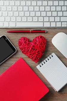 Periféricos de computadora con corazón de mimbre rojo, portátiles y teléfono móvil en la mesa de madera