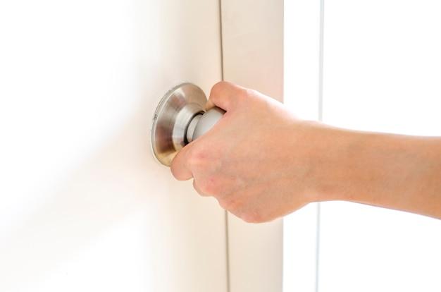 Perilla de puerta abriendo a mano, puerta blanca