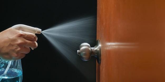 Perilla de la puerta de limpieza con alcohol en aerosol para la prevención de covid-19 (coronavirus)