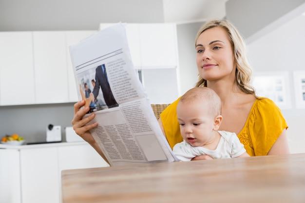 Periódico de la lectura de la madre con el bebé en la cocina