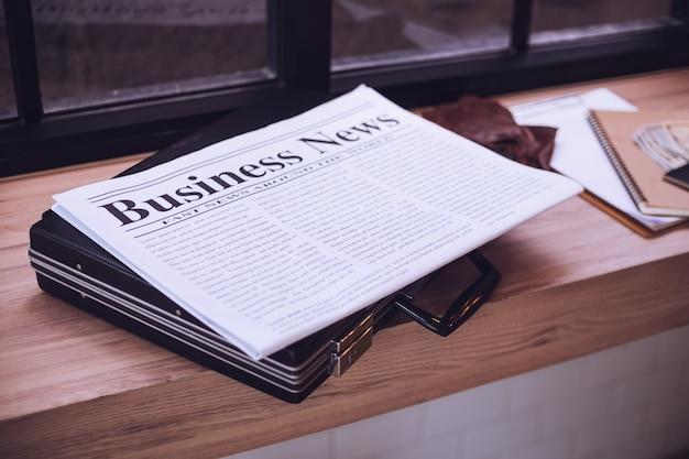 Periódico, maletín en una mesa de madera en la cafetería