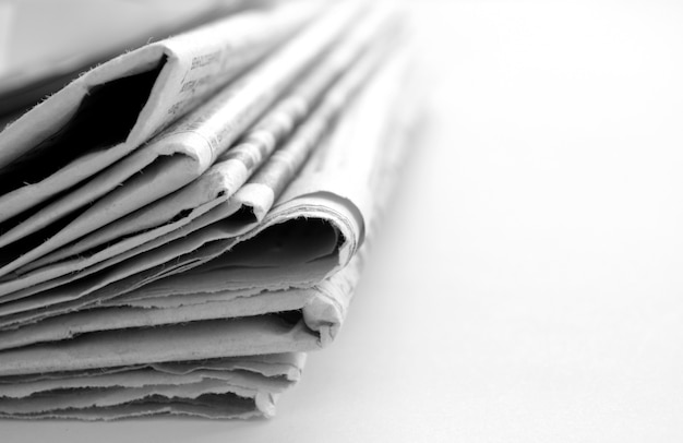 Periódico con noticias de cerca sobre fondo blanco.