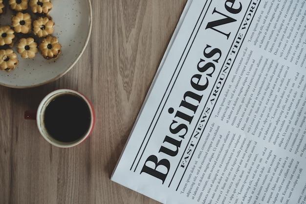 Periódico, una taza de café y aperitivos en una mesa de madera.
