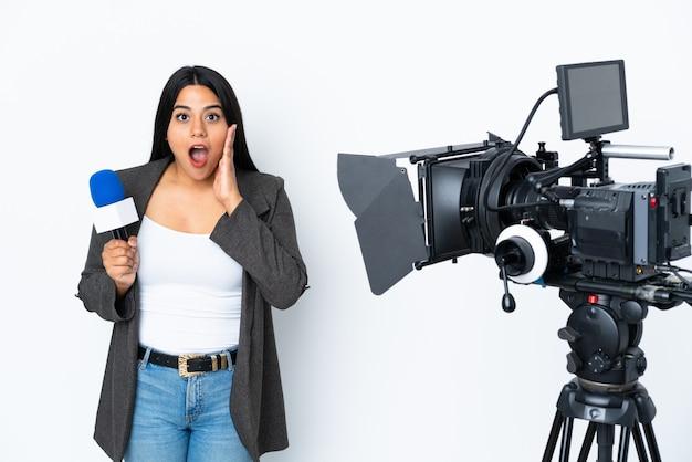 Periodista colombiana sosteniendo un micrófono y reportando noticias en blanco