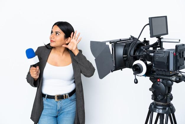 Periodista colombiana sosteniendo un micrófono y reportando noticias en la pared blanca escuchando algo poniéndose la mano en la oreja