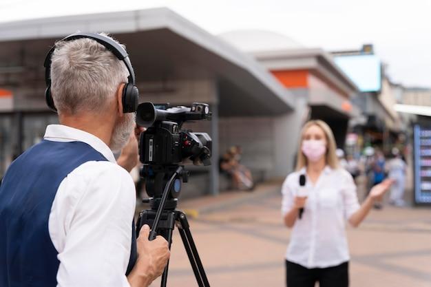 Periodista contando las noticias al aire libre