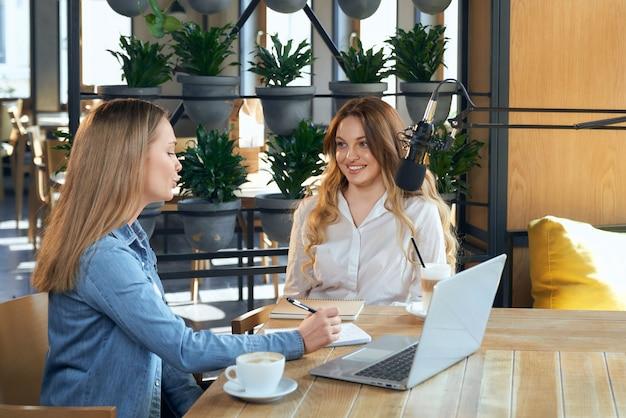 Periodista dando preguntas a la mujer bloguera en el café.