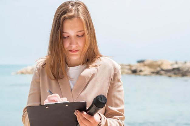 Periodista femenina de pie junto al mar