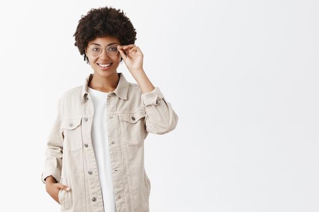 Periodista inteligente y creativa con camisa beige y gafas, tocando el borde de las gafas, sonriendo, sosteniendo la mano en el bolsillo, segura de sí misma y satisfecha con un gran resultado