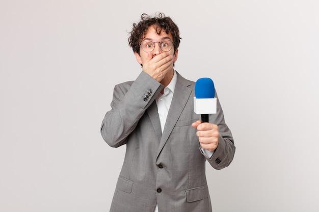 Periodista joven cubriendo la boca con las manos con un sorprendido