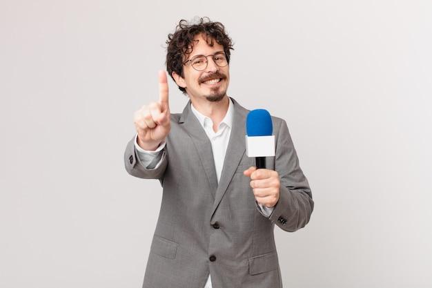 Periodista joven sonriendo con orgullo y confianza haciendo el número uno