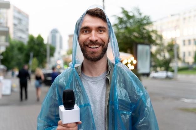 Periodista masculino de vista frontal sosteniendo un micrófono