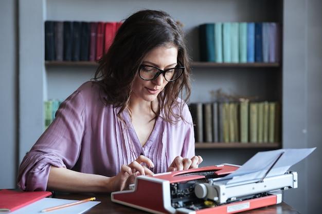 Periodista morena mujer madura en anteojos escribiendo en máquina de escribir en interiores