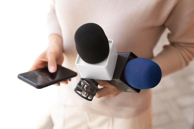 Periodista de vista frontal sosteniendo un micrófono