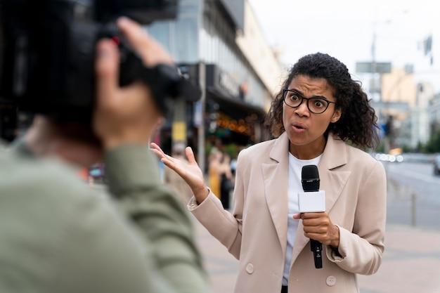 Periodista de vista frontal tomando una entrevista