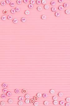 Perlas del alfabeto borde fondo rosa