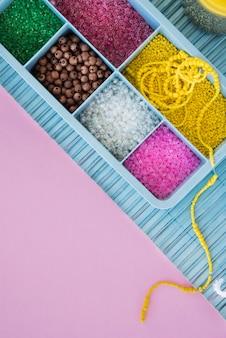 Perlas de colores en caja azul en mantel sobre el fondo rosa
