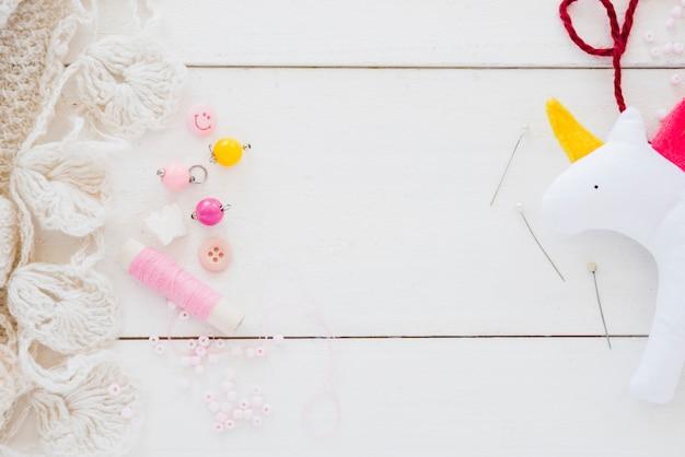 Perlas de colores; carrete; aguja y trapo unicornio en escritorio de madera blanca