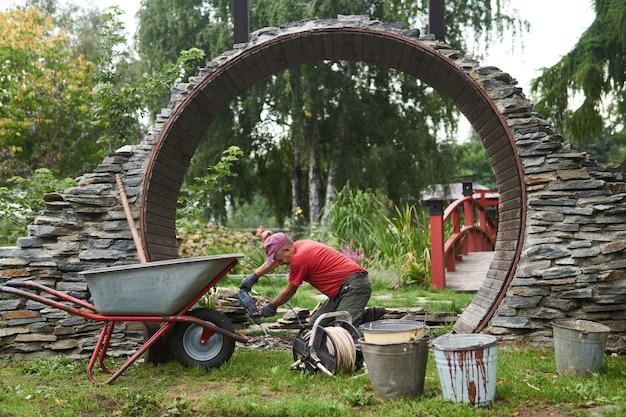 Perm, rusia - 01 de septiembre de 2020: trabajador construye una entrada redonda llamada puerta de la luna en un jardín de estilo chino