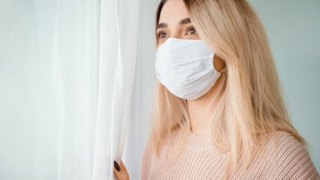 Permanecer en el interior mujer con máscara médica blanca