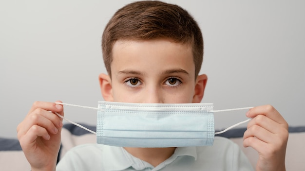 Permanecer en el interior niño con máscara médica