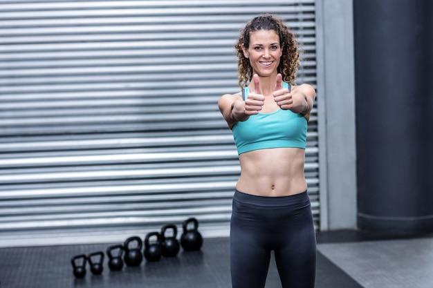 Permanente mujer muscular gesticular pulgares arriba