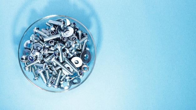 Pernos, tuercas y arandelas de diferentes tamaños en un recipiente de vidrio sobre un fondo azul.