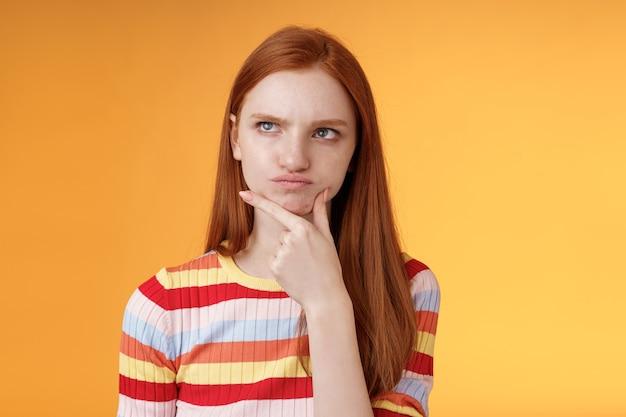 Perpleja, vacilante, de aspecto serio, niña pelirroja, ojos azules, pesadillas, opciones, fruncir el ceño, tocar la barbilla, mirar, esquina superior izquierda, pensamiento reflexivo, desconcertado, solución, ponderando la decisión, fondo naranja.