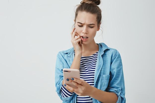 Perplejo, preocupado, lindo, joven, de 25 años, mujer, verificar, lista de facturas en línea, fruncir el ceño, preocupado, morder, dedo, mirar, teléfono inteligente, preocupado, mente calculadora