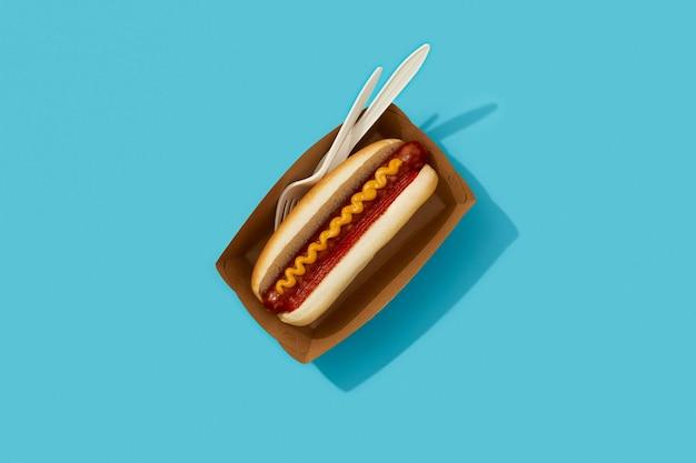 Perrito caliente clásico con salsa de tomate salchicha y mostaza sobre fondo azul menú de restaurante entrega tacke awa ...