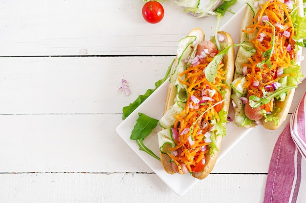 Perrito caliente con pepino, zanahoria, tomate y lechuga en la mesa de madera. vista superior