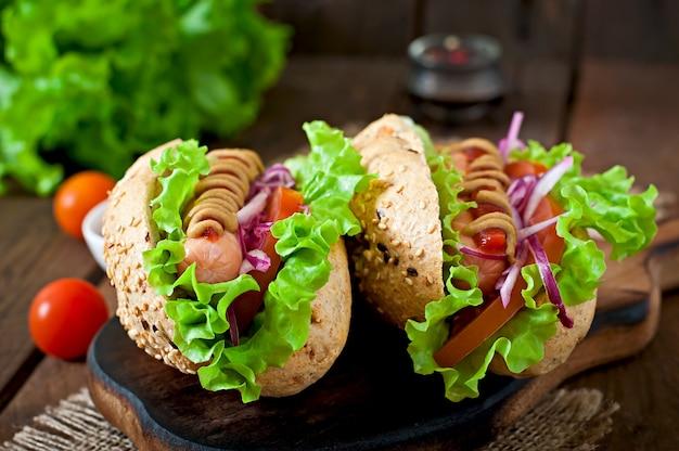 Perrito caliente con salsa de tomate mostaza y lechuga en la mesa de madera.