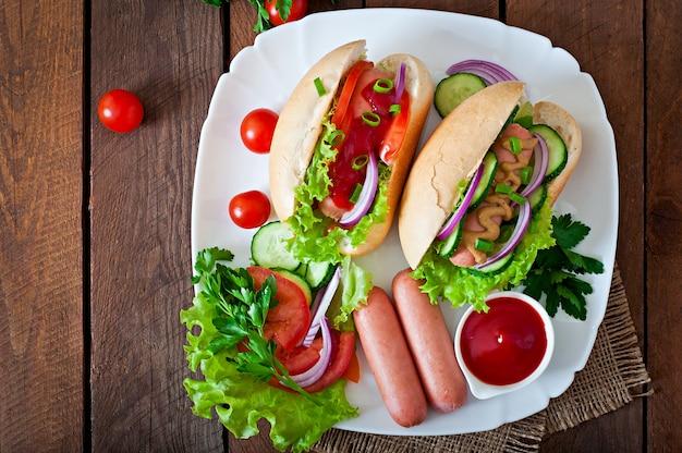 Perrito caliente con salsa de tomate, mostaza, lechuga y verduras en la mesa de madera
